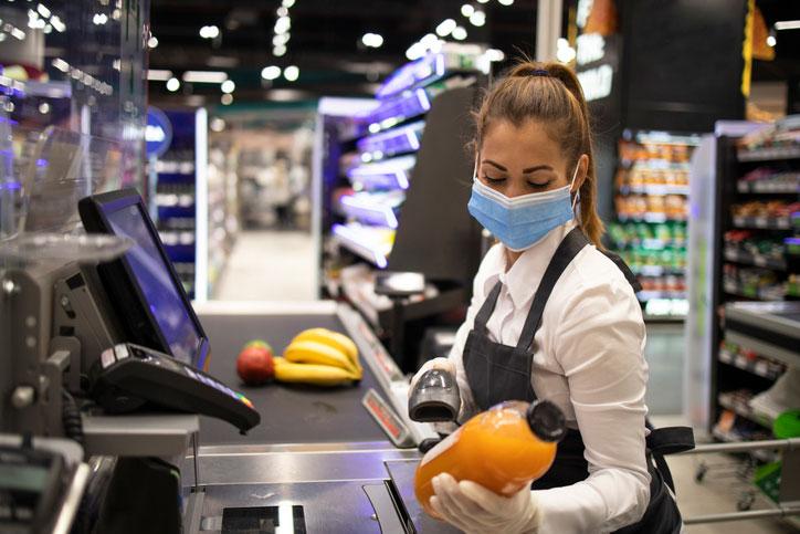 vrouw scant producten aan lopende band van voedingswinkel