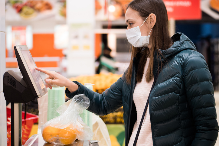 Vrouw gebruikt weegschaal in supermarket